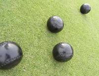 Roll on: An 'end' of bowls (above), after each player has tried to get their bowl closest to the white 'jack' — as they are on the green at Yokohama Country & Athletic Club (below). | BRETT BULL PHOTOS
