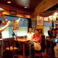 'An Englishman walks into a bar . . . ': Britons Jay Hoare and John McBride (below) perform standup at The Hobgoblin pub in Shibuya. | NATE JENSEN PHOTOS