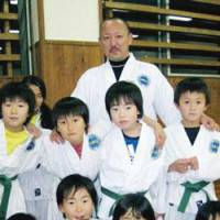 Naotaka Aoki poses with his tae kwon do students at a class in Kamakura, Kanagawa Prefecture. | KRIS KOSAKA PHOTO