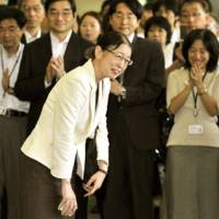 Happy return: Atsuko Muraki is greeted by delighted colleagues at the Health, Labor and Welfare Ministry in Tokyo after being reinstated as a government employee in September 2010. She now holds a senior position in the Cabinet Office. | KYODO PHOTO
