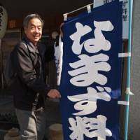 A Kashima visitor shows off a sign for catfish dishes.