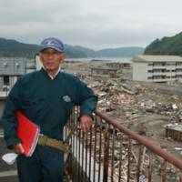 For the record: Yoshinobu Ryokawa stands atop his building in Unosumai recently with an album of photos he took before and during the March 11 tsunami. | EDAN CORKILL PHOTO