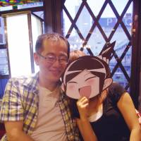 Real-life character: Junichi Inoue and his wife, Yue, hiding behind a mask, are seen in Tokyo's Ikebukuro district on Sunday. Inoue's real-life manga has become so popular on the Internet that they feel they need to hide her face in order to live ordinary lives. | REIJI YOSHIDA PHOTO