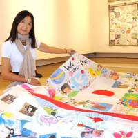 Creating for others: Film director Linda Ohama holds one of the quilts made by Canadian and Japanese children in support of survivors of the March 11 earthquake and tsunami, at the Canadian Embassy in Tokyo. The exhibition 'Canada-Tohoku Kids to Kids Cloth Letters' will be held at the embassy through Dec. 13. | SATOKO KAWASAKI PHOTO