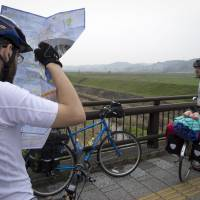 Day 3: Dylan Gunning checks the map as Scott Keenan takes a breather during their bicycle trip across Japan, just a month after the Great East Japan Earthquake of March 2011. | ANDREW MARSTON