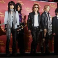 Seeing double: Members of X Japan line up with their wax lookalikes at Madame Tussauds Tokyo on Monday. From left: Pata, Heath, Yoshiki, Toshi and Sugizo. | MIKE SUNDA