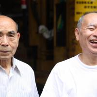 Like father, like son: 62-year-old Yasuo Suzuki (right), owner of goods delivery service Kounsha, laughs at the suggestion that he and his 94-year-old father Yoshihisa Suzuki (left) look like brothers.