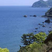 Sea the sights: A short walk from Atami Station, up a narrow road that takes you through a tunnel, rewards those who forsake the town's more material delights with beautiful views such as this of Sagami Bay and wooded headlands on the lip of an extinct volcano falling away steeply into the ocean. | STEPHEN MANSFIELD PHOTO