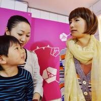 Idol chitchat: A humanoid robot speaks to a child and his mother Wednesday at a department store in the city of Osaka. | KYODO