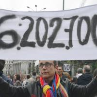 Labor pains: A protester holds a banner with a reference to the latest jobless figure in Spain during a May Day protest in Madrid on Wednesday. | AFP-JIJI