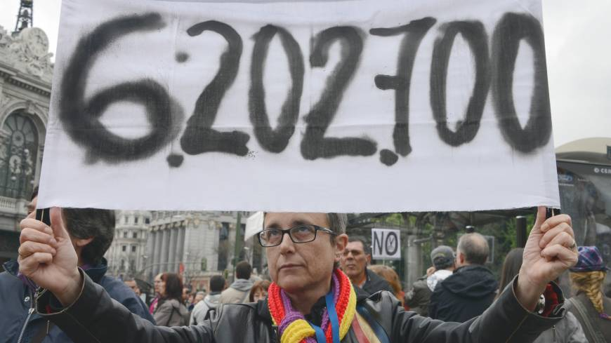 Labor pains: A protester holds a banner with a reference to the latest jobless figure in Spain during a May Day protest in Madrid on Wednesday.