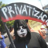 An El Salvador university student in San Salvador protests against privatization during a Labor Day rally on Wednesday. | AFP-JIJI