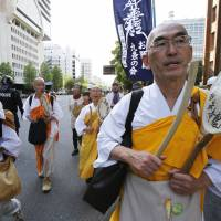 Off the warpath: Buddhist monks participate in a march against Prime Minister Shinzo Abe's calls to amend the war-renouncing Constitution in Tokyo on the Constitution Day holiday Friday. Hundreds of people, young and old, gathered downtown for a peaceful protest against Abe's efforts to give the government more power to abridge civil liberties. | AP