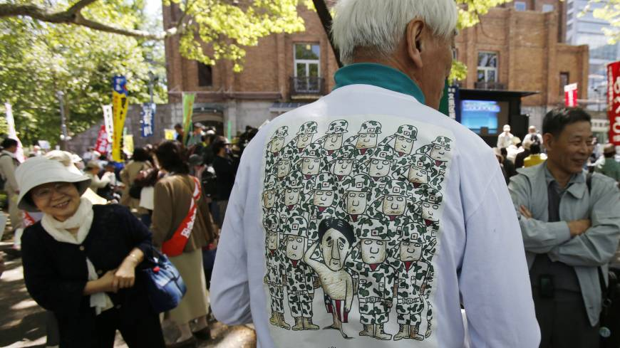 A protester shows off a T-shirt depicting him in Stars and Stripes underwear saluting Self-Defense Forces personnel at Friday's rally in Tokyo.
