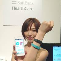 Wrist strong: A model wears a Fitbit flex wristband that can send health and fitness information to a Softbank smartphone. | KAZUAKI NAGATA