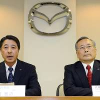 Change at the top: Mazda Motor Corp. Senior Managing Executive Officer Masamichi Kogai (left) announces plans Thursday in Hiroshima for him to replace President Takashi Yamanouchi (right). | KYODO