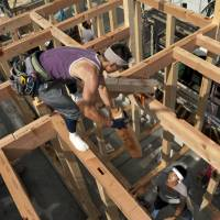 Tax stimulus: Carpenters work at a new home construction site in Yokohama last July. Major homebuilders expect their sales and profits to rise in fiscal 2013 thanks to a projected surge in housing demand ahead of a planned consumption tax hike next April. | BLOOMBERG