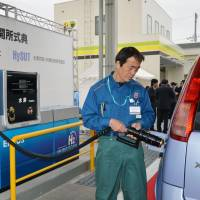 Full-service future: A worker at a gas station pumps hydrogen into a fuel cell car in April in Ebina, Kanagawa Prefecture. The station, operated by JX Nippon Oil & Energy Corp., is the first in the nation to offer both gasoline and hydrogen fuel. | KYODO