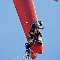 Rotating shifts: Two maintenance workers control the rotor blades of a wind turbine near Sieversdorf, eastern Germany, on Thursday. The wind turbine is about 90 meters tall, and one rotor blade is 36 meters long. | AFP-JIJI