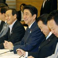 Facts and figures: Prime Minister Shinzo Abe and members of his Cabinet attend a ministerial meeting on the government's monthly economic report at the Prime Minister's Office on Monday. | KYODO