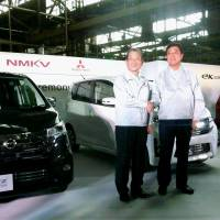 A car is born: Nissan Motor Co.'s Chief Operating Officer Toshiyuki Shiga (left) and Mitsubishi Motors Corp. President Osamu Masuko shake hands Monday in front of a DAYZ minicar their companies developed in Kurashiki, Okayama Prefecture. | KYODO