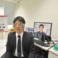 Future is now: An employee at NTT DoCoMo Inc.'s research and development center in Yokosuka, Kanagawa Prefecture, demonstrates a hands-free video phone. | KAZUAKI NAGATA