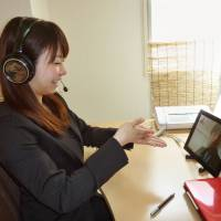 Quiet and clear: A sign-language interpreter with ShuR Co. assists someone through its Internet-based service from the company's office in Fujisawa, Kanagawa Prefecture. | KYODO