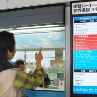 Value for money: A Japanese traveler checks foreign exchange rates at Narita airport on May 10. The weak yen has impacted the nation's travel industry. | KYODO