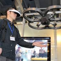 You are there: Wearing a head-mounted display, a reporter tries out the Flying Head miniature helicopter at Sony Computer Science Laboratories Inc.'s open house in Tokyo last week. | YOSHIAKI MIURA