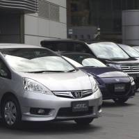 Upping the ante: Honda Motor Co. vehicles are displayed outside the company's headquarters in Tokyo in late April. The firm said Friday it will add a hybrid version of the Accord in the lineup in the domestic market on June 21. | BLOOMBERG