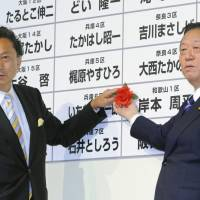 Color of success: Yukio Hatoyama, head of the Democratic Party of Japan, and his deputy, Ichiro Ozawa, attach a rose next to the name of a winning candidate in the August 2009 Lower House election. | KYODO PHOTOS