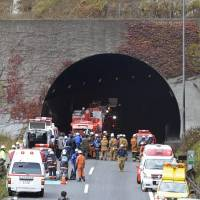 Expressway nightmare: Police, firefighters and ambulance crews converge on the Sasago Tunnel on the Chuo Expressway in Yamanashi Prefecture Sunday after a 50-meter section of its ceiling collapsed, triggering vehicle fires and trapping several motorists. | KYODO