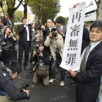 A Mainali supporter raises a sign reading 'acquitted in retrial' in front of the Tokyo High Court after its ruling the same day. | KYODO