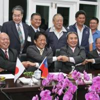 Shared interest: Ishigaki Mayor Yoshitaka Nakayama (front row, second from left) and local fishing cooperative chief Chen Chun-sheng (third from left) join hands in Suao, a fishing port in Taiwan, on Nov. 13 during talks over fishing rights in waters near the Senkaku Islands in the East China Sea. | KYODO