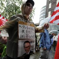Flag-wavers: Members of a rightist group Zaitokukai raise naval flags during a rally in Tokyo on Sep. 23. | AFP-JIJI