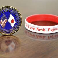 A coin made by Fujisaki as a gift for the American people to show Japan's gratitude for their postdisaster support and a rubber bracelet he received from a U.S. official are seen.
