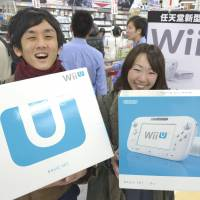 Game on: Customers at a store in the city of Osaka show off the Nintendo Wii U game consoles they bought Saturday. | KYODO