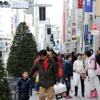 Rare sight: Chinese tourists walk in the Ginza shopping district in Tokyo on Dec. 2. | AFP-JIJI