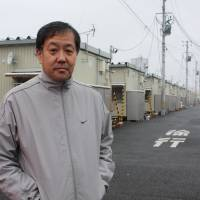 Masahiro Iitsuka stands outside the temporary housing complex he is staying at in Taihaku Ward, Sendai, where he also heads the residents association. | SETSUKO KAMIYA