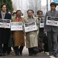 Seeking balance: Lawyers led by Hidetoshi Masunaga (center) hold signs pointing out the disparity in vote values between the most- and least-populated districts as they walk to the Tokyo High Court on Monday. | KYODO