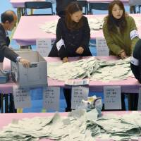 An election administration commission counts votes Sunday in Minato Ward, Tokyo. | KYODO
