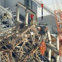 Plant cleanup: A remote-controlled crane removes damaged steel beams above a spent nuclear fuel pool in the reactor 3 building at Tokyo Electric Power Co.'s Fukushima No. 1 nuclear plant Thursday. | KYODO