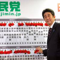 Comeback: Liberal Democratic Party President Shinzo Abe stands in front of a board showing the names of the party's winning candidates in the Dec. 16 Lower House election at LDP headquarters in Tokyo. | YOSHIAKI MIURA