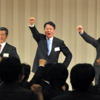 Changed game: Former trade minister Banri Kaieda, who won the Democratic Party of Japan's presidential race, gives a show of party unity Tuesday flanked by Sumio Mabuchi (left), who ran unsuccessfully against him, and Prime Minister Yoshihiko Noda at a Tokyo hotel. | YOSHIAKI MIURA