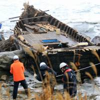 Lost: Police officers check an open wooden boat that washed ashore on Sado Island, Niigata Prefecture, on Nov. 29 and is believed to have originated in North Korea. | KYODO