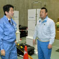 In your debt: Prime Minister Shinzo Abe (left) voices his gratitude to a worker at J Village in Fukushima Prefecture before visiting the Fukushima No. 1 nuclear plant Saturday. | KYODO