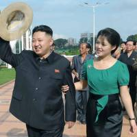 Making waves: North Korean leader Kim Jong Un and his wife, Ri Sol Ju, inspect an amusement park in Pyongyang in July. | KCNA / KYODO