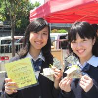 Sweet charity: Mayuko Sako and Saki Nishino of Free The Children Japan sell chocolates at a Tokyo street performance festival in Suginami Ward on Sunday. A portion of the proceeds will be used to help build a school in India. | COURTESY OF FREE THE CHILDREN JAPAN