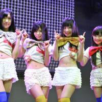 Blue chips: Machikado Keiki Japan members (from left) Hinako Kuroki, Kanon Mori, Yuki Sakura and Jun Amaki show how they shortened their costumes to reflect the rise in the Nikkei stock average. | YOSHIAKI MIURA