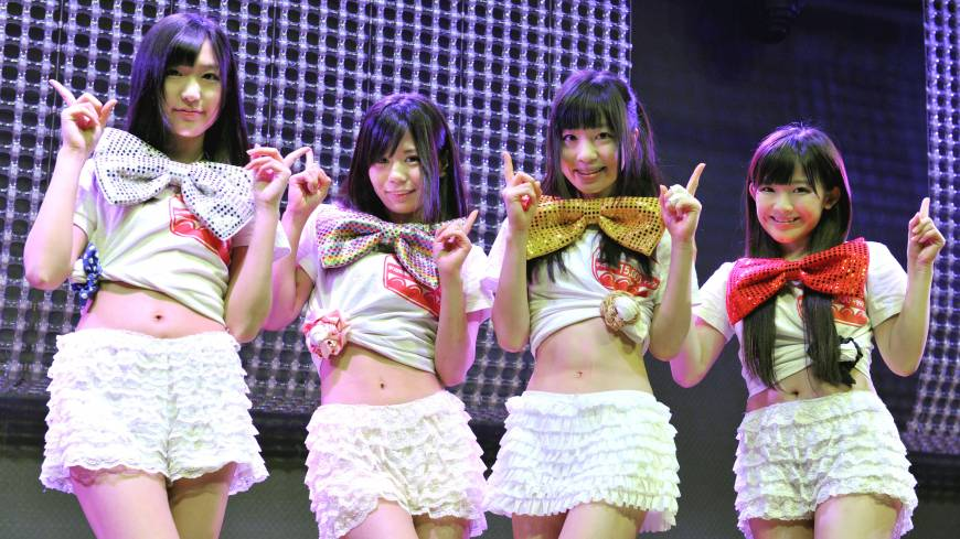 Blue chips: Machikado Keiki Japan members (from left) Hinako Kuroki, Kanon Mori, Yuki Sakura and Jun Amaki show how they shortened their costumes to reflect the rise in the Nikkei stock average.